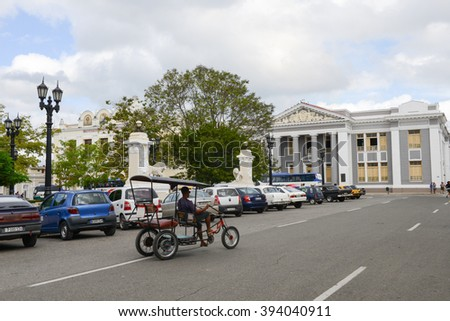 Cienfuegos, Cuba - 18 January 2016: People riding a bike in front of San Lorenzo school building on Jose Marti square park in Cienfuegos, Cuba