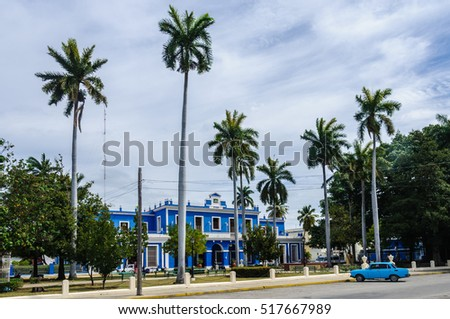 CIENFUEGOS, CUBA - MARCH 22, 2016: Blue colonial building and palm trees in Cienfuegos, Cuba