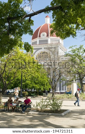 CIENFUEGOS, CUBA - MAY 7, 2014: Town hall of Cienfuegos city at Jose Marti park with some locals in Cienfuegos, Cuba