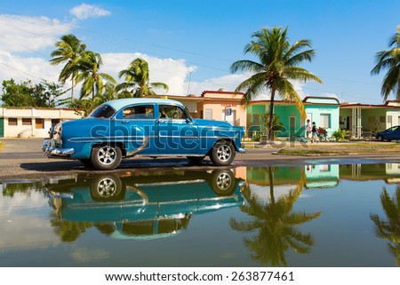 CIENFUEGOS - FEBRUARY 22: Streets of Cienfuegos with classic old car and palm tree in background on February 22, 2015 in Cienfuegos. Old American cars are iconic sight of Cuba street. - stock photo