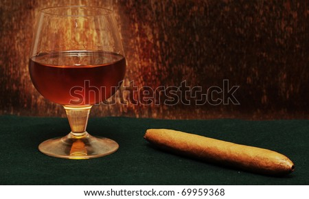 cigar and a glass of alcohol on green fabric