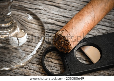 Cigar and Cutter with Glass of Brandy or Whiskey on Wooden Background - stock photo
