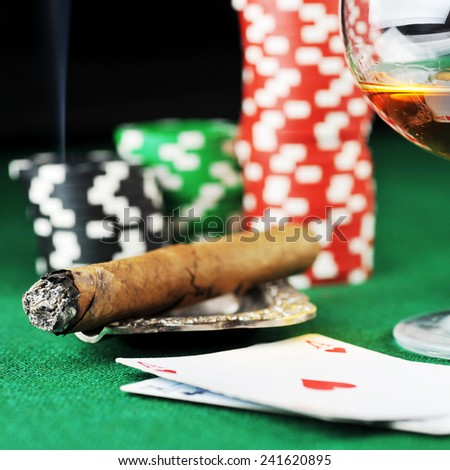 Cigar, chips, drink and playing cards on green - stock photo