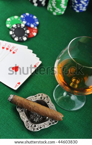 Cigar, chips for gambling, drink and playing cards on green - stock photo