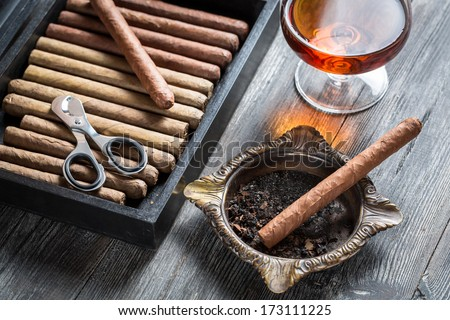 Cigar in ashtray and cognac - stock photo