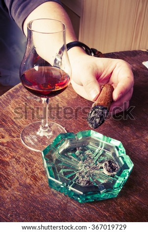 cigar in man hand with glass of alcohol and green ashtray. on the retro wooden table - stock photo