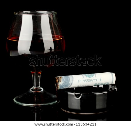 Cigar of the 100 dollar bill and an ashtray and glass of brandy isolated on black - stock photo