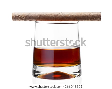 Cigar on a glass of whisky, alcoholic drink with a tobacco product on a white background, nobody. - stock photo