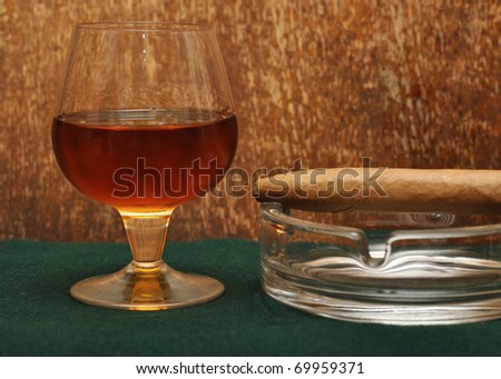 Cigar on the glass with alcohol on green fabric