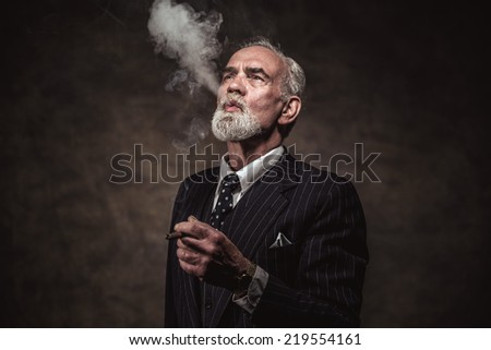 Cigar smoking characteristic senior business man with gray hair and beard wearing blue striped suit and tie. Against brown wall. - stock photo