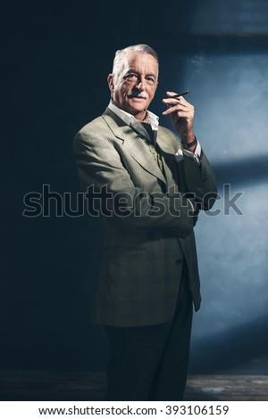Cigar smoking retro 1940 senior businessman. Studio shot. - stock photo