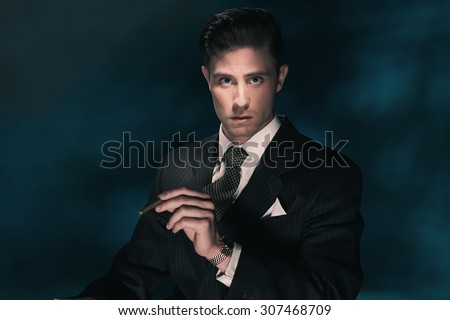 Cigar smoking vintage businessman in suit and tie. Hair combed back. Against dark blue background. - stock photo