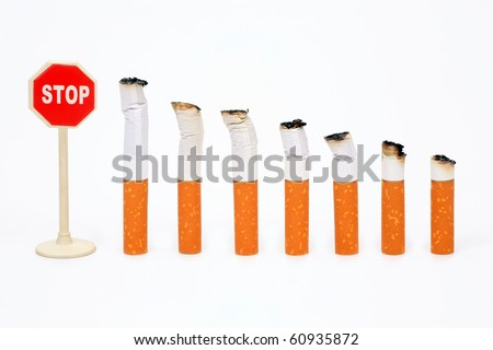 "Cigaret stubs standing in a row before a sign ""Stop"" on a white background - stock photo"