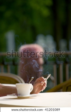 Cigarette a cup a hand - stock photo