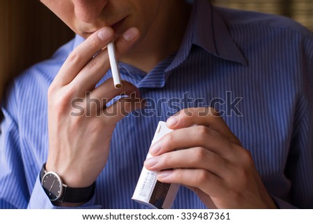 Cigarette addiction. Tobacco nicotine smoke. Unhealthy, danger, bad, narcotic habit. White filter. Health risk, cancer illness. Quit, stop toxic drug. Lifestyle concept. Pack in hand. - stock photo