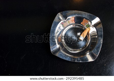 Cigarette and ashes in a silver metal ashtray on black background - stock photo