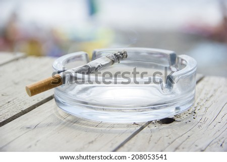 Cigarette and ashtray on wooden table - stock photo