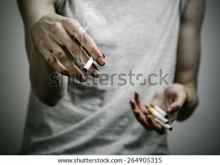 Cigarette and drug addiction topic: smoker holds the cigarette in his hand on a dark background in the studio - stock photo