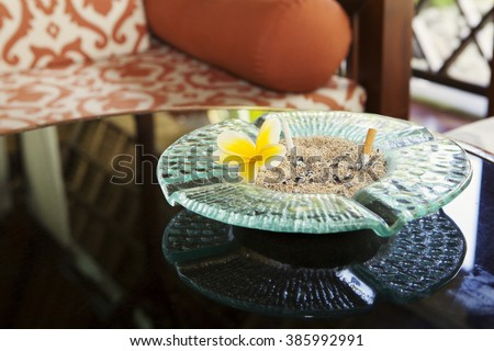 Cigarette and glass hotel ashtray on table with frangipani flower - stock photo