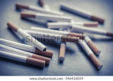 Cigarette arrangement on green grungy wood surface, tobacco industry background - stock photo