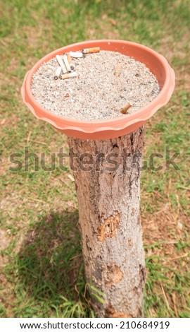 Cigarette ashtray on old trunk - stock photo