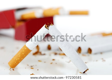 Cigarette boken in half in front with the cigarette pack and cigarettes in the background - stock photo