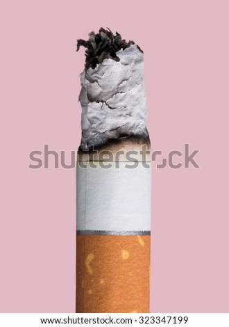 Cigarette burning on pink background, smoke addiction concept - stock photo