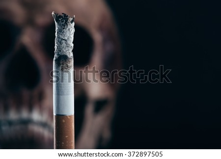 Cigarette burning with human old skull on background, stop smoking and disease concept - stock photo