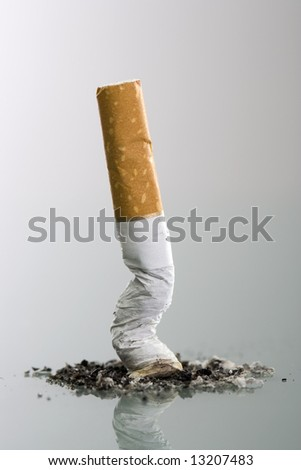 Cigarette butt end crushed into ashtray - grey background - stock photo