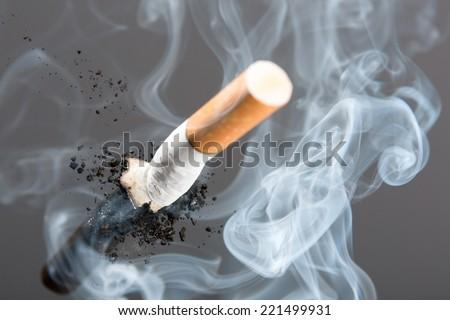 Cigarette butt in smoke - stock photo
