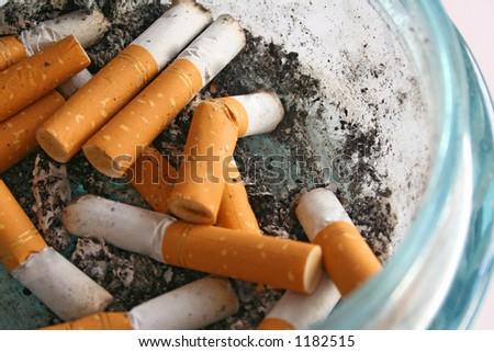 Cigarette butts in a glass ashtray. - stock photo