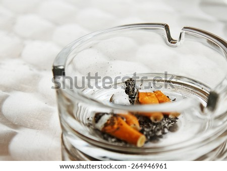 Cigarette butts in a glass ashtray, smoking in public places - stock photo