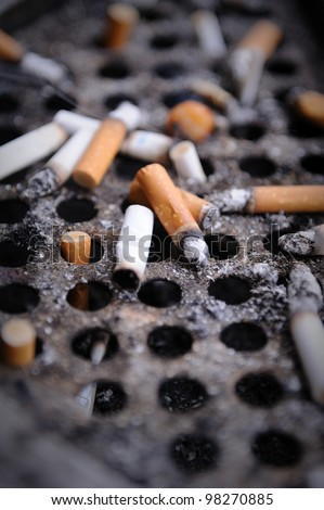 Cigarette butts stuck in dirty ash - stock photo