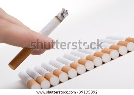 Cigarette in a hand with sigarettes backround
