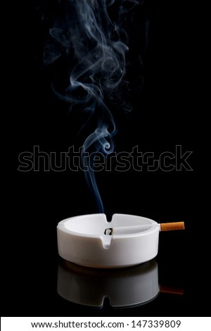 Cigarette in an ashtray on a black background - stock photo