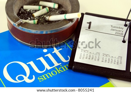 Cigarette in and stop smoking literature near calendar open to January 1st. - stock photo