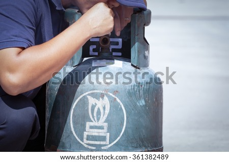 Cigarette in hand near gas tank cylinder can ignition of flammable, safety concept - stock photo