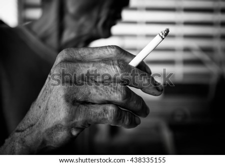 Cigarette in old hand, Unhealthy,Cancer, Secondhand,Blurry portrait,Black and white - stock photo