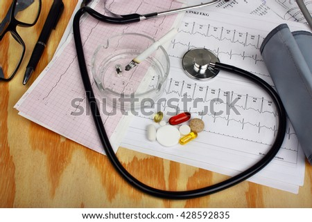 Cigarette in the ashtray and stethoscope, blood pressure monitor, pills and pen on electrocardiogram chart.