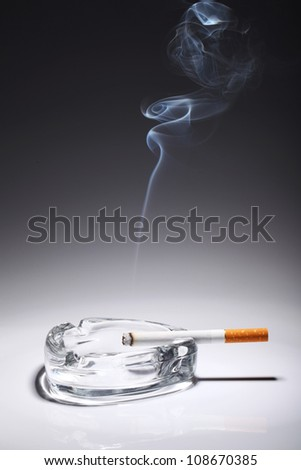Cigarette in the ashtray over gray gradient - stock photo