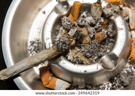 Cigarette laying in ashtray, ashtray is filled with other cigarettes and ash. Healthy life concept - stock photo
