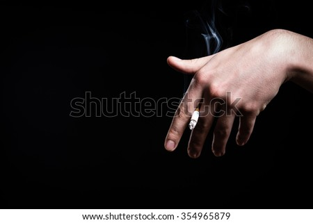 Cigarette nicotine addiction.Smoking a fag,cigarette butt.Unhealthy,danger,bad narcotic habit.Health risk,cancer illness.Young man smoking tobacco cigarette.Hand holding a cigarette smoke.Vice - stock photo