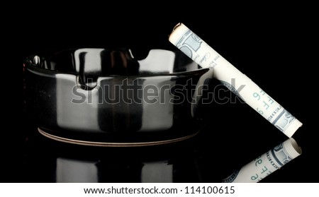 Cigarette of the 100 dollar bill and an ashtray isolated on black - stock photo