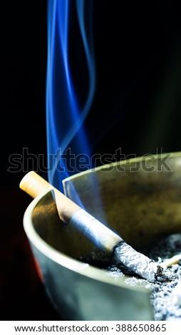 Cigarette on ashtray with a beautiful blue wisp of smoke - stock photo