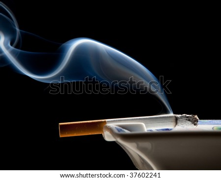Cigarette on ashtray with a beautiful wisp of smoke - stock photo