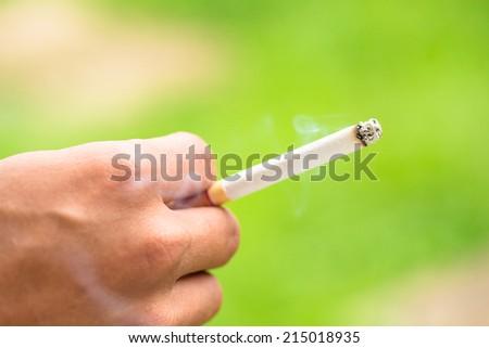 Cigarette on smoker hand - stock photo