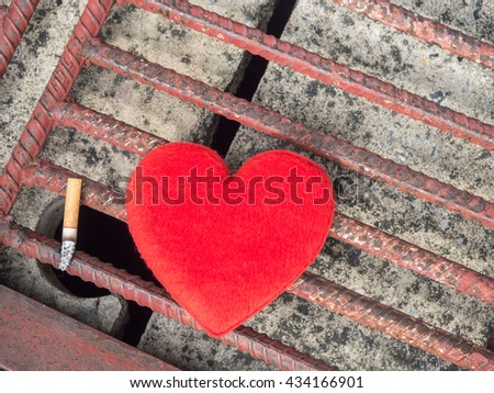 Cigarette stub and Red heart,Heart-shaped red put on the rusty steel of the drain.Stop Smoking Concept. - stock photo