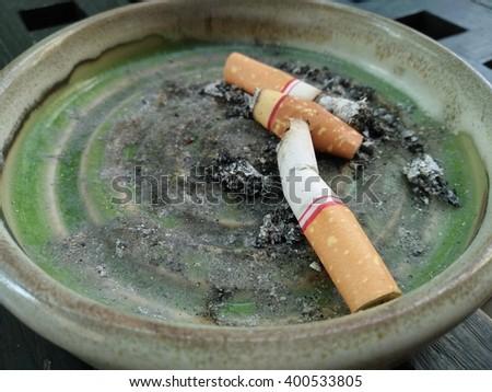 Cigarette stub in ash tray. - stock photo