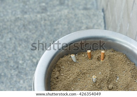cigarette stub in ash tray with space for text - stock photo