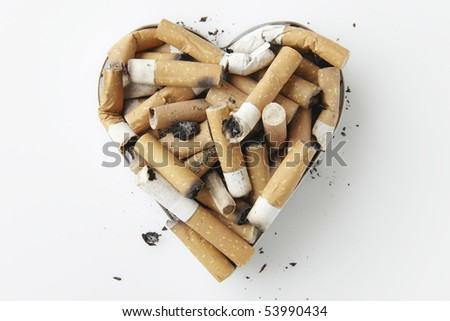 cigarette stubs in a metal heart shaped ashtray - stock photo